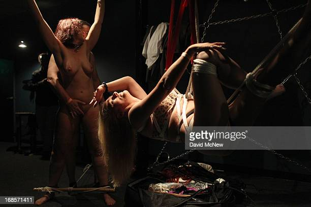 A participant called Dalbin makes dancelike moves as she is suspended in ropes at a dungeon party during the domination convention DomConLA in the...