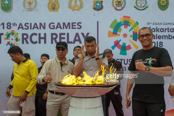 Participant carries the Asian Games torch relay in Pekanbaru on August 2 in Riau Province Indonesia The 18th Asian Games is scheduled to begin in...