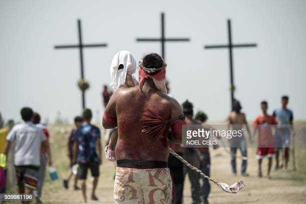 TOPSHOT A participant carrying his daughter walks to the crosses during a reenactment of the crucifixion of Jesus Christ during Good Friday...