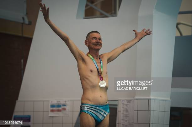 A participant celebrates his medal during the synchronized swimming contest during the 10th edition of the international Gay Games at the Maurice...