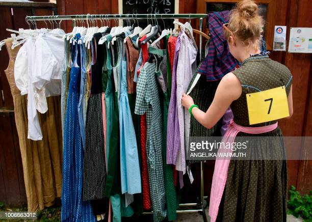 """Participant choses a rental Dirndl before competing in the """"Dirndl-Flugtag"""" fun event in Mittenwald, southern Germany, on July 28, 2018. - A jury..."""