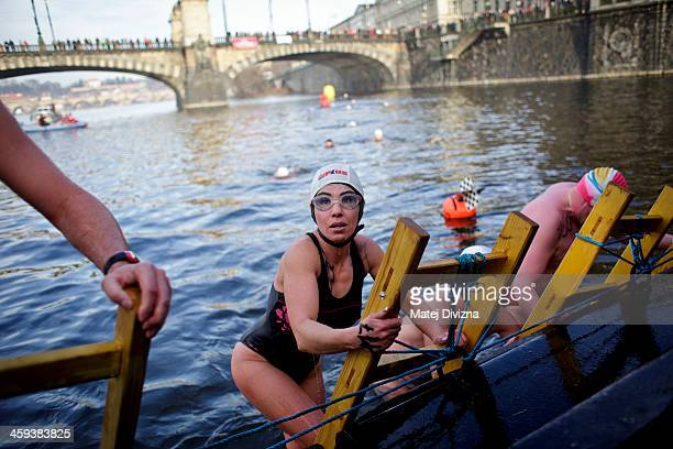 A participant climbs a ladder to leave the Vltava river during the traditional Christmas winter swimming competition named in memory of Alfred...