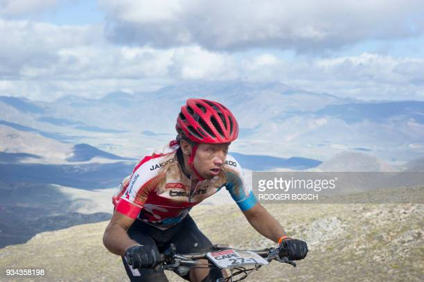 A participant climbs the highest pass during the first full stage of the 2018 Cape Epic African Mountain Bike Race on March 19 in the mountainous...