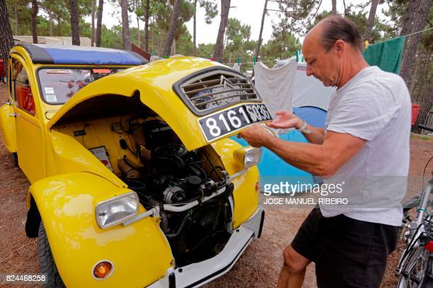 Participant closes the hood of his Citroen classic car 2CV before the parade at Ericeira village during the World 2017 2CV Meeting July 30, 2017. -...