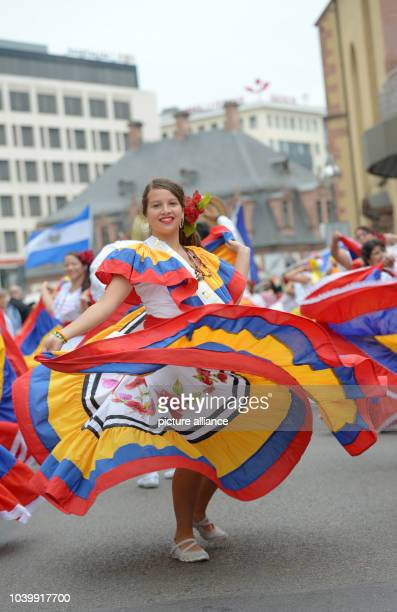 A participant costumed in traditional Colombian clothing dances during the 'parade of cultures' in Frankfurt/Main Germany 28 June 2014 The parade...