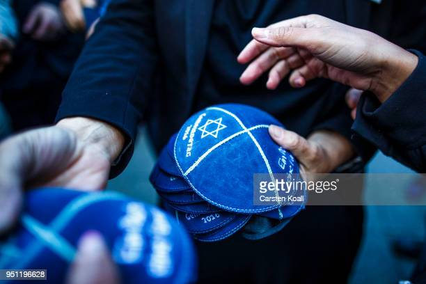 A participant distributes kippahs to other participants during a 'wear a kippah' gathering to protest against antiSemitism in front of the Jewish...