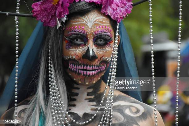 A participant dressed as a Catrina dances during a parade as part of the Day of the Dead celebration at Avenida Reforma on October 27 2018 in Mexico...