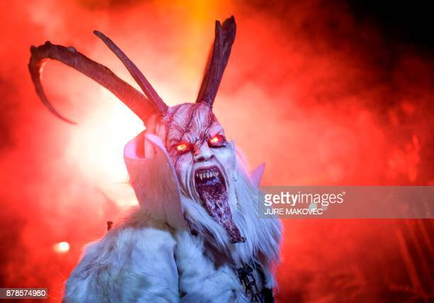 A participant dressed as a 'Krampus' creature walks during 'The Hike of the Krampus of Three Lands' in Podkoren Slovenia on November 24 2017 / AFP...