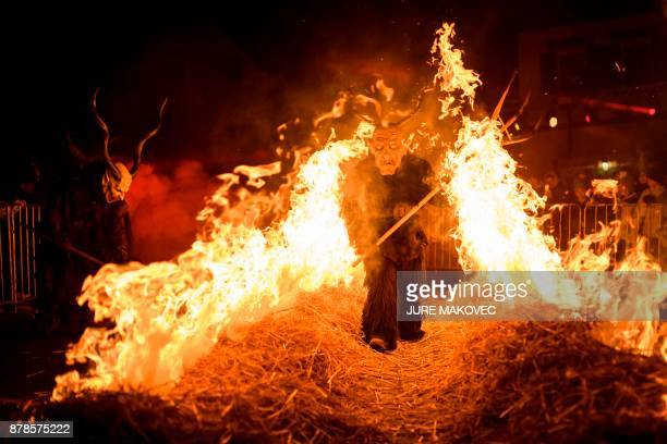 A participant dressed as a 'Krampus' creature walks through fire during 'The Hike of the Krampus of Three Lands' in Podkoren Slovenia on November 24...