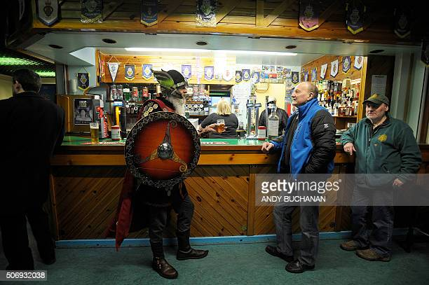 A participant dressed as a Viking has a drink in a pub before the annual Up Helly Aa festival in Lerwick Shetland Islands on January 26 2016 Up Helly...