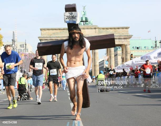 A participant dressed as Jesus runs in front of Brandenburger Gate during the 41th edition of the Berlin Marathon in Berlin on September 28 2014 AFP...