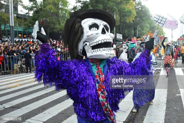 A participant dressed as skull dances during a parade as part of the Day of the Dead celebration at Avenida Reforma on October 27 2018 in Mexico City...