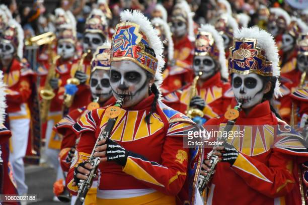 A participant dressed as skull plays the flute during a parade as part of the Day of the Dead celebration at Avenida Reforma on October 27 2018 in...