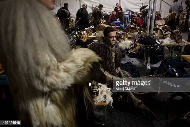 A participant dressed as the Krampus creature waits for a start of Krampus gathering on November 22 2014 in Schladming Austria Krampus is a demonlike...