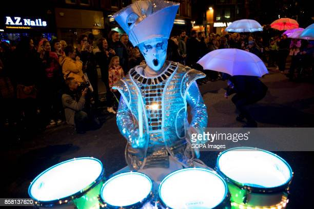 A participant dressed in white lighting costume is seen playing lighting drums during the Leeds Festival Light Night Leeds is an annual free...