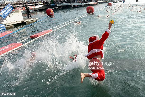A participant dressed up as Santa Claus jumps into the water during the106th edition of the Copa Nadal in Barcelona's Port Vell on December 25 2015...