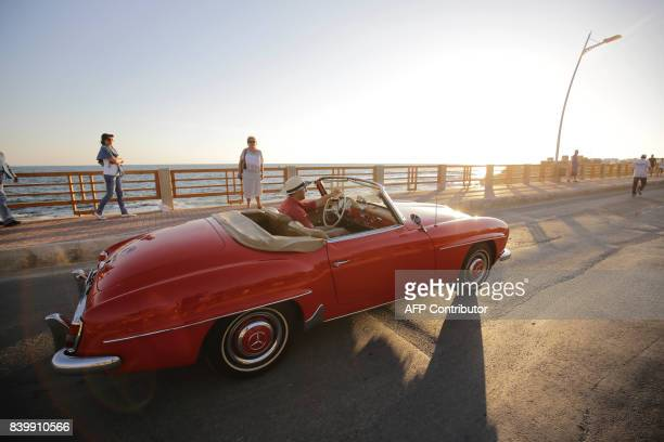 A participant drives a Mercedes 190SL during the Collection Cars Parade event in the Lebanese coastal city of Amchit on August 27 2017 / AFP PHOTO /...