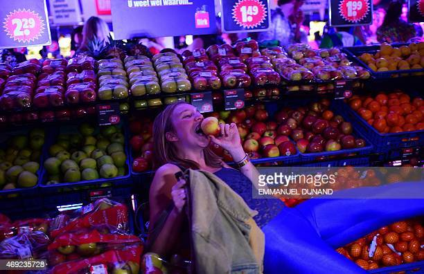A participant eats an apple during a disco groceries party a concept which turns a supermarket into a night club after its closing time in Amsterdam...
