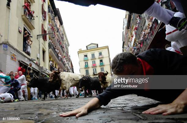 A participant falls down as Fuente Ymbro's fighting bulls turn Estafeta curve during the fourth bull run of the San Fermin festival in Pamplona...