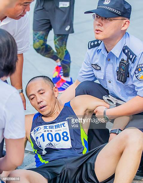 A participant falls down during the 2015 Beijing Marathon on September 20 2015 in Beijing China