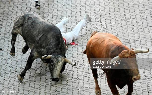 A participant falls next to Cebada Gago fighting bulls on the third day of the San Fermin bull run festival in Pamplona northern Spain on July 9 2018...