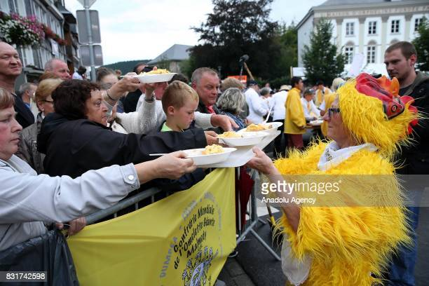 A participant give plates with omlette to the people after the Members of the World Brotherhood of the Huge Omelet cooked giant omlette within a 4...