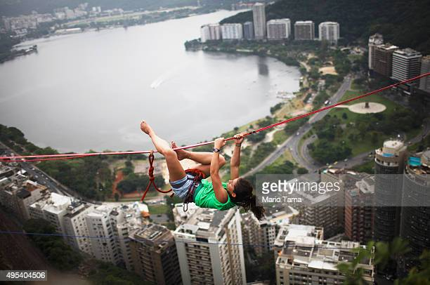 A participant hangs on a slackline set up between rocks in the Cantagalo favela community during the Highgirls Brasil festival on November 2 2015 in...