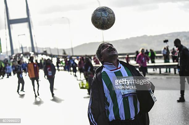 TOPSHOT A participant heads a ball on the July 15 Martyrs' Bridge known as the Bosphorus Bridge during the 38th annual Istanbul Marathon on November...
