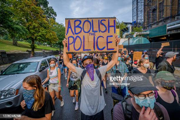 Participant holding a Abolish Police sign at the protest. A coalition of activists and organizations led by activist, poet, and organizer Selu...