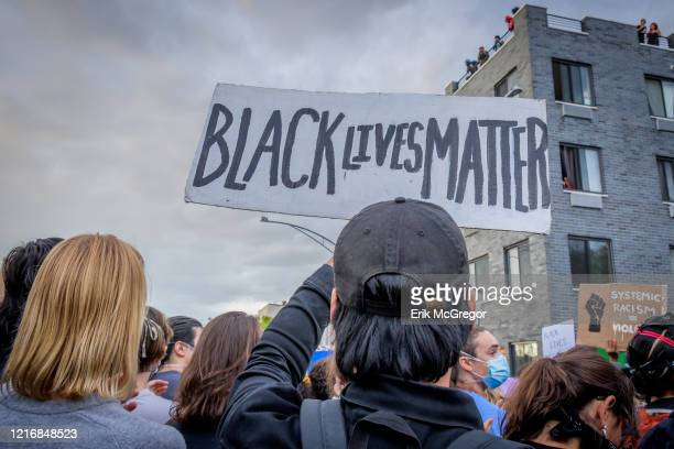 A participant holding a Black Lives Matter sign at the protest Hundreds of protesters gathered flooded the streets of Crown Heights in Brooklyn to...