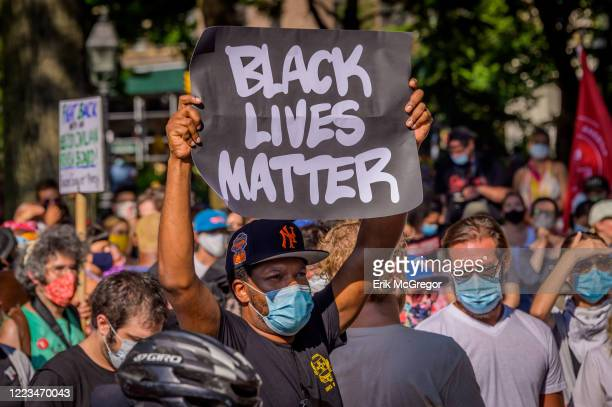 A participant holding a Black Lives Matter sign at the protest On the eve of the NYC budget decision hundreds of protesters gathered at Washington...
