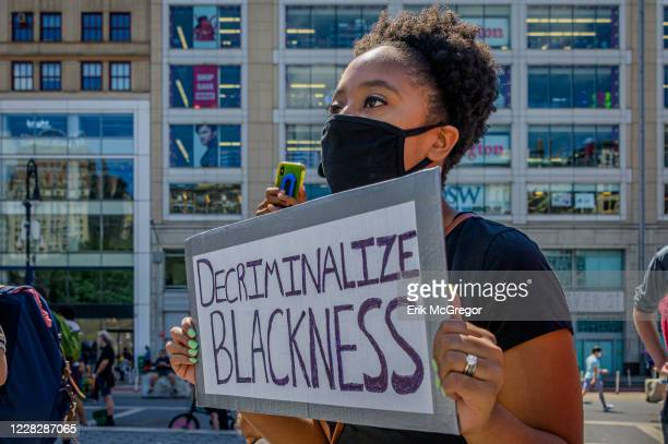 Participant holding a Decriminalize Blackness sign at the protest. Gays Against Guns , the direct action, gun violence prevention group formed by...