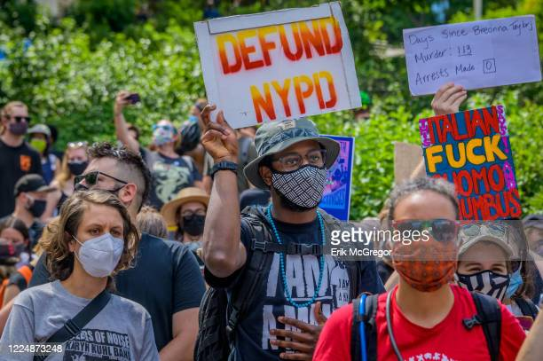 A participant holding a Defund NYPD sign at the protest Thousands of New Yorkers joined the Coalition to Honor Black and Indigenous Activists at Fort...
