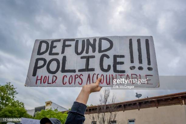 A participant holding a Defund Police sign at the protest Hundreds of protesters gathered flooded the streets of Crown Heights in Brooklyn to demand...