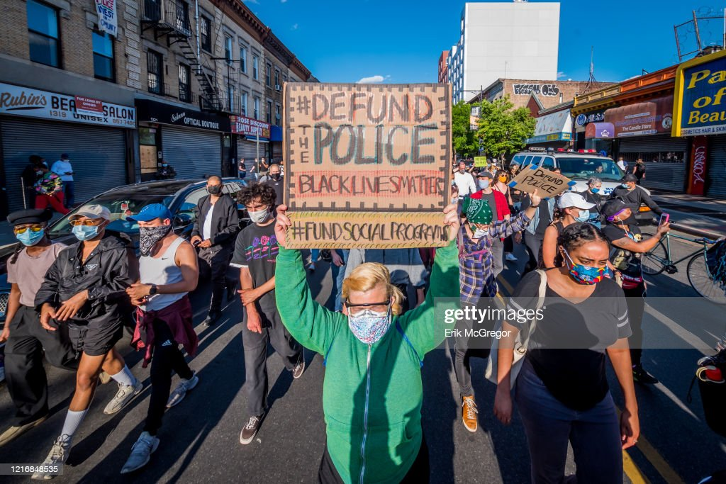 A participant holding a Defund Police sign at the protest. : News Photo