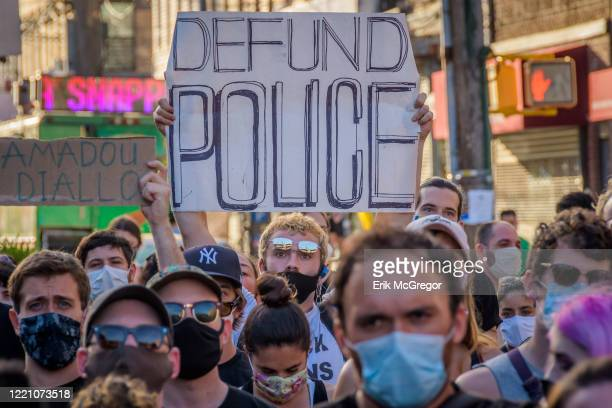 A participant holding a Defund Police sign at the protest Hundreds of protesters gathered at Wyckoff Plaza for a rally and march in the streets of...