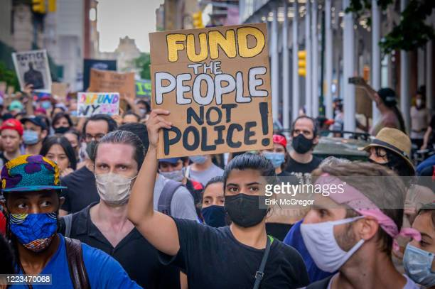 Participant holding a Defund Police sign at the protest. On the eve of the NYC budget decision, hundreds of protesters gathered at Washington Square...