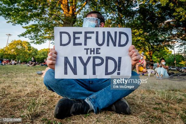 A participant holding a Defund The Police sign at the protest Greenpoint residents gathered at McCarren Park for a socially distancing rally and...