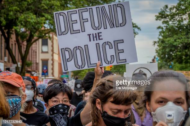 A participant holding a Defund The Police sign at the protest Thousands of protesters filled the streets of Brooklyn in a massive march to demand...