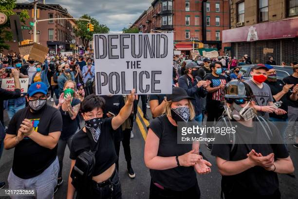 Participant holding a Defund The Police sign at the protest. Thousands of protesters filled the streets of Brooklyn in a massive march to demand...
