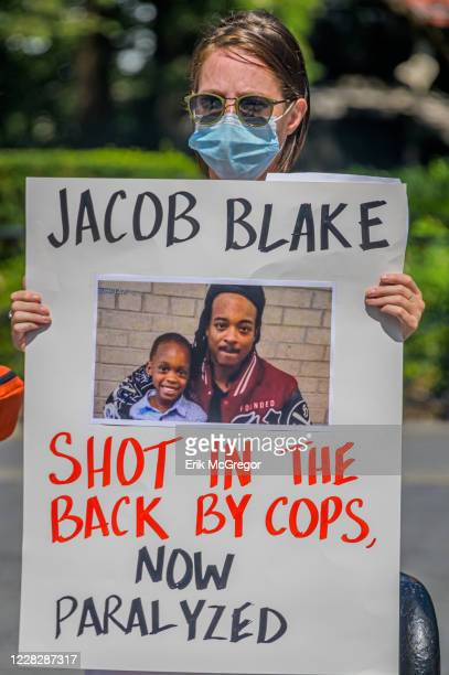 Participant holding a Jacob Blake sign at the protest. Gays Against Guns , the direct action, gun violence prevention group formed by members of...