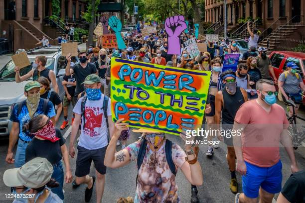 A participant holding a Power To The People sign at the protest Thousands of New Yorkers joined the Coalition to Honor Black and Indigenous Activists...
