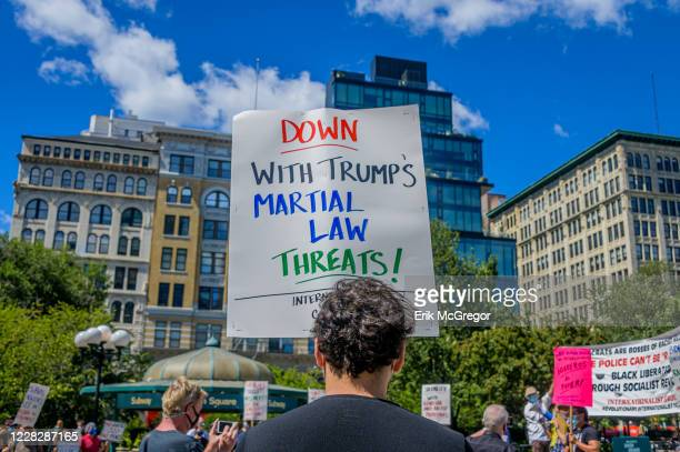 Participant holding a sign against Trump's martial law threats at the protest. Gays Against Guns , the direct action, gun violence prevention group...