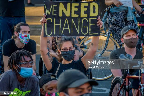 Participant holding a We Need Change sign at the protest.Hundreds of protesters gathered at Wyckoff Plaza for a rally and march in the streets of...