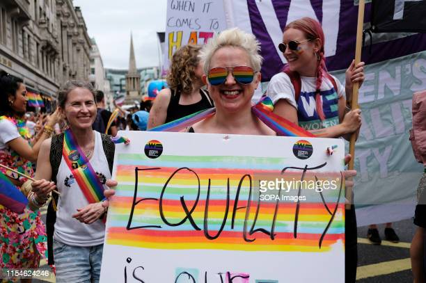 A participant holds a banner saying Equality during the parade Thousands of revellers filled Londons streets with colour to celebrate Pride in the...