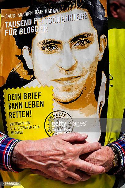 A participant holds a banner with the conterfei of blogger Raif Badawi as he demonstrates outside the Saudi Arabian Embassy against the recent Saudi...