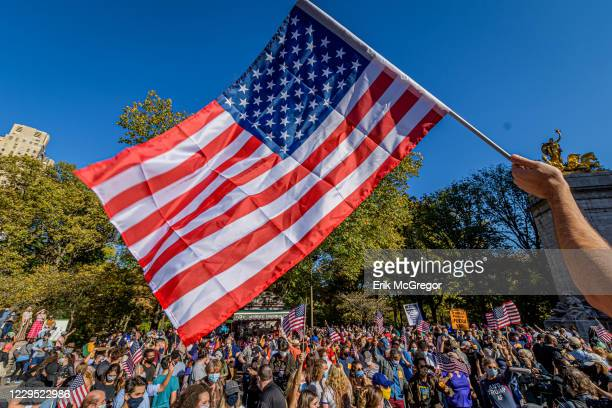 Participant holds a flag over the crowd of thousands at the celebration march. Thousands of New Yorkers joined members of the Protect the Results:...