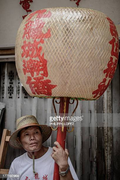 A participant holds a lantern during a parade for the Hungry Ghost Festival in Hong Kong on August 22 2013 The festival celebrated in the seventh...