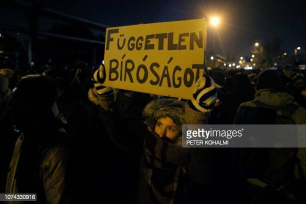 A participant holds a placard reading 'We want independent court of justice' outside the headquarters of the Hungarian state television during a...