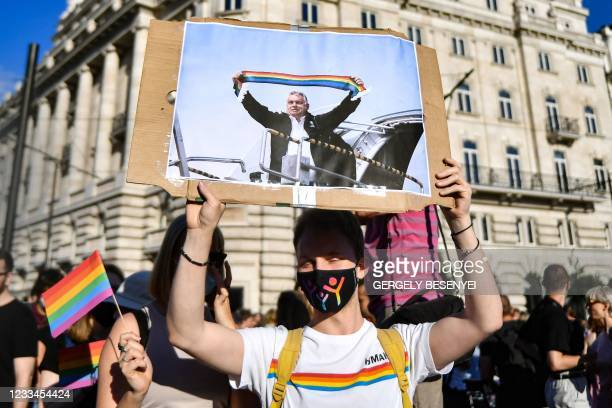 Participant holds a placard showing Hungarian Prime Minister Viktor Orban holding a scarf in rainbow colours, in front of the parliament building in...
